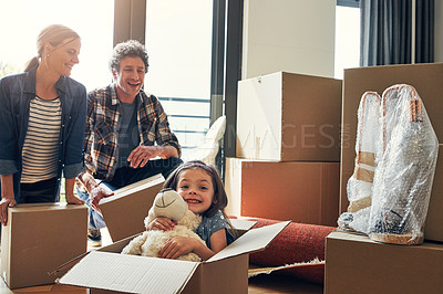 Buy stock photo Portrait of a cheerful loving family packing out boxes together in their new home during the day