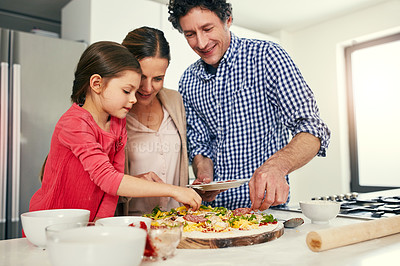 Buy stock photo Shot of a cheerful family preparing a pizza together to go into the oven in the kitchen at home