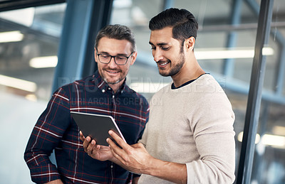 Buy stock photo Shot of two businessmen using a digital tablet in an office