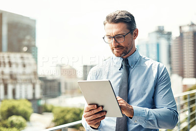 Buy stock photo Shot of a mature businessman using a digital tablet outside on the balcony of his office