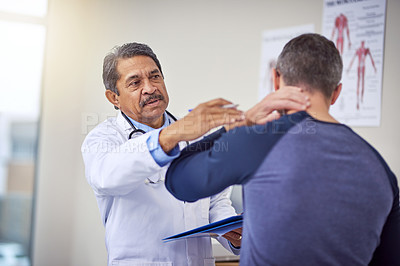 Buy stock photo Shot of a confident mature male doctor doing a checkup on a patient while standing inside of a hospital during the day