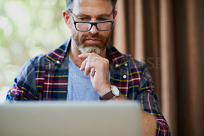 Buy stock photo Cropped shot of a handsome mature man using a laptop at home