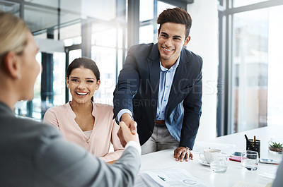 Buy stock photo Cropped shot of two businesspeople shaking hands during a meeting in the boardroom