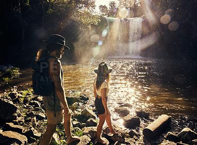 Buy stock photo Shot of a young couple walking along rocks at a lake