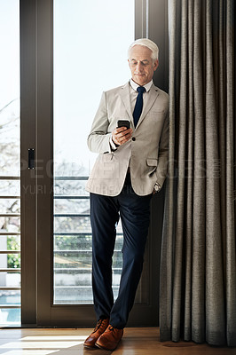 Buy stock photo Shot of a cheerful mature businessman standing with his one hand in his pocket while texting on his phone inside of a house during the day