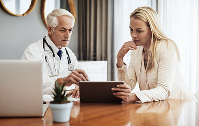 Buy stock photo Shot of a confident mature male doctor consulting with a businesswoman while making use of a digital tablet at a table during the day