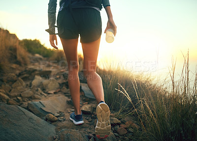 Buy stock photo Rearview shot of an unrecognizable woman out for a run along a mountain trail