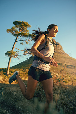 Buy stock photo Shot of a young woman out for a run along a mountain trail