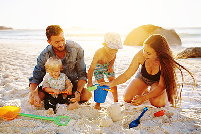 Buy stock photo Shot of a family building sandcastles together at the beach