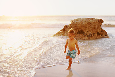 Buy stock photo Shot of an adorable little boy playing at the beach