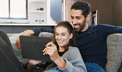 Buy stock photo Shot of a happy young couple using a digital tablet while relaxing together at home