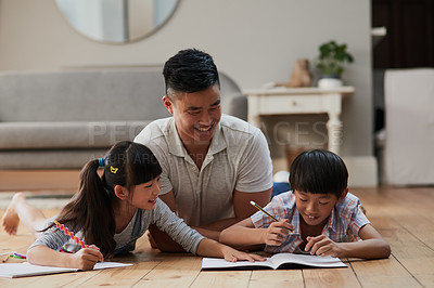 Buy stock photo Shot of a cheerful father and his two children doing homework together while lying on the floor at home during the day