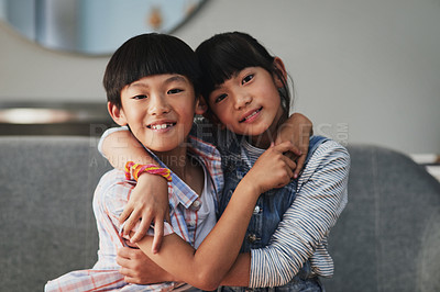 Buy stock photo Portrait of a cheerful brother and sister holding each other while being seated on a couch at home during the day
