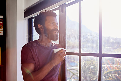 Buy stock photo Shot of a cheerful young man standing next to a window and looking through it while drinking a cup of coffee inside at home during the day