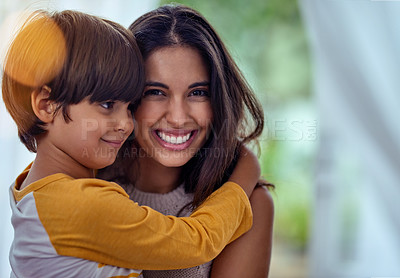 Buy stock photo Shot of an adorable little boy affectionately hugging his mother at home