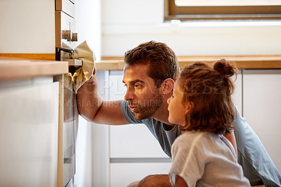 Buy stock photo Cropped shot of a father and daughter looking at what they had baked in the oven at home