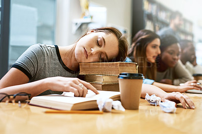 Buy stock photo Shot of a young woman looking tired while studying in a college library