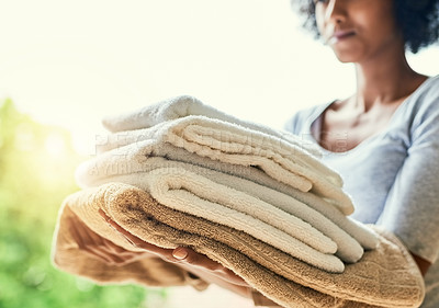 Buy stock photo Cropped shot of an unrecognizable woman holding folded towels at home
