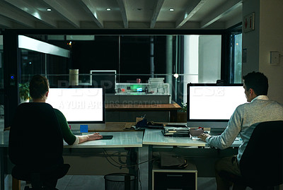 Buy stock photo Rearview shot of two businesspeople working on computers in an office at night