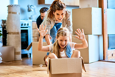 Buy stock photo Shot of a cheerful young woman pushing her daughter around in a box imagining its a car inside at home during the day