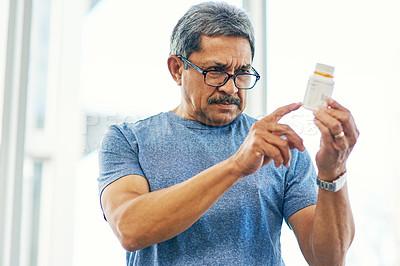 Buy stock photo Cropped shot of a handsome senior man reading a bottle of prescription medication