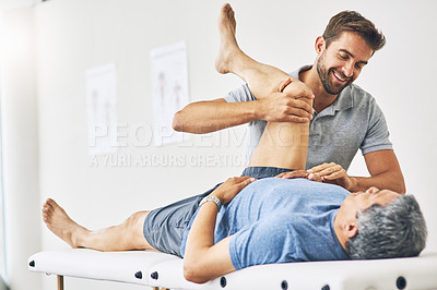 Buy stock photo Cropped shot of a young male physiotherapist assisting a senior patient in recovery