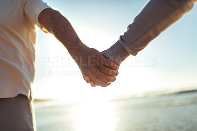 Buy stock photo Cropped shot of an older couple holding hands at the beach