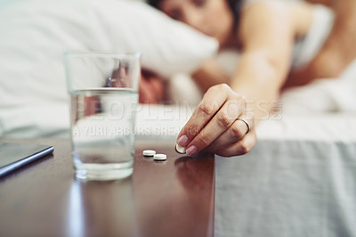 Buy stock photo Shot of an unrecognizable woman lying in bed and taking a pill to drink after waking up sleeping in bed