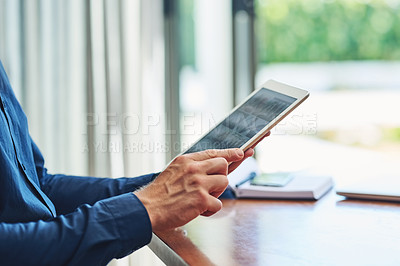 Buy stock photo Shot of an unrecognizable person browsing on a digital tablet while being seated at a table at home