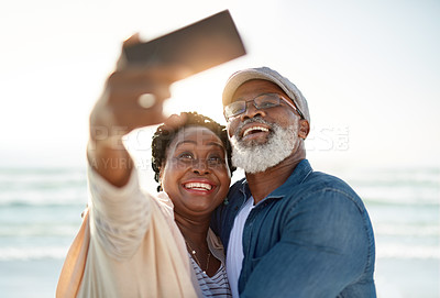 Buy stock photo Shot of a mature couple taking selfies together at the beach