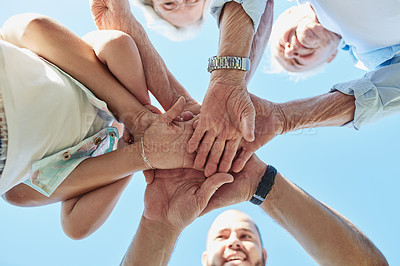 Buy stock photo Low angle shot of a happy family joining their hands together outdoors