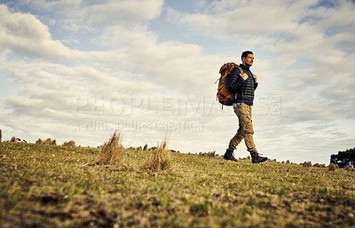 Buy stock photo Full length shot of a handsome young man hiking through the mountains