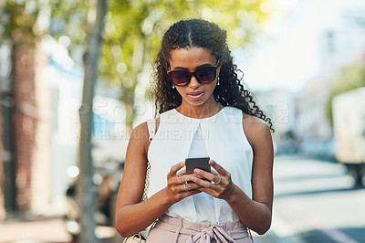 Buy stock photo Shot of an attractive young woman using a cellphone in  the city