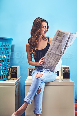 Buy stock photo Shot of an attractive young woman reading the newspaper in a laundry room while waiting for washing to be done during the day