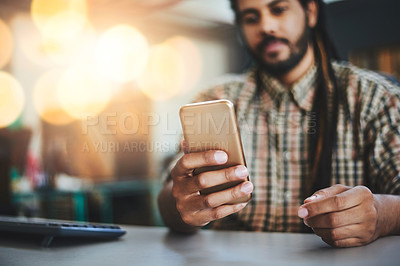 Buy stock photo Cropped shot of a young male designer sending a text while sitting in his office