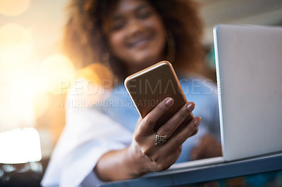 Buy stock photo Cropped shot of a young female designer sending a text while sitting in her office