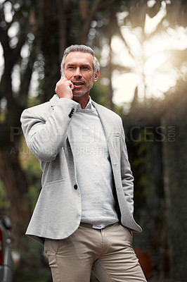 Buy stock photo Cropped shot of a smartly dressed mature businessman on a call outside