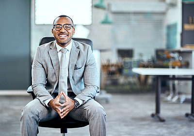 Buy stock photo Portrait of a young businessman sitting on a chair in an office