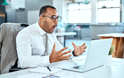 Buy stock photo Shot of a young businessman looking surprised while working on a laptop in an office