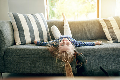Buy stock photo Portrait of an adorable little girl relaxing on the sofa at home