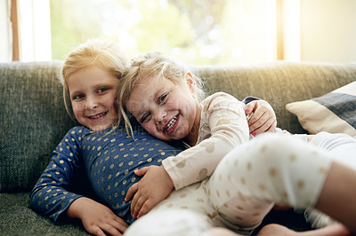Buy stock photo Portrait of two adorable little girls relaxing on the sofa at home