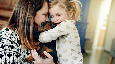 Buy stock photo Shot of a mother and her little daughter bonding with their dog at home