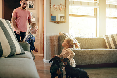 Buy stock photo Shot of a father and his two little daughters playing with their dogs at home