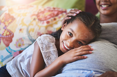 Buy stock photo Portrait of an adorable little girl resting on her mother's pregnant stomach at home