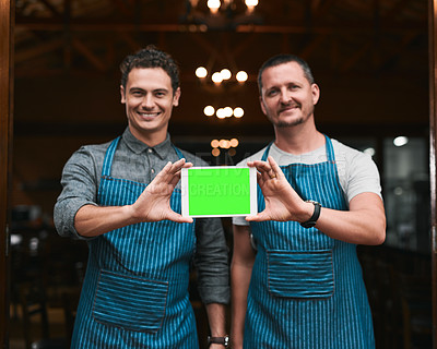 Buy stock photo Portrait of two cheerful businessmen holding up a digital tablet together while standing in front of the doors of a beer brewery