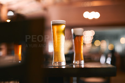 Buy stock photo Shot of two glasses of beer standing on its own at a table  inside of a beer brewery during the day