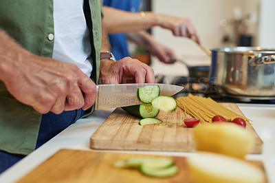 Buy stock photo Closeup shot of an unrecognizable man slicing cucumbers while cooking with his wife at home
