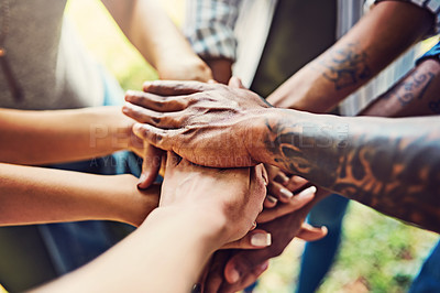 Buy stock photo Closeup shot of an unrecognizable group of people joining their hands in a huddle outdoors