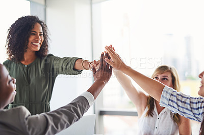 Buy stock photo Cropped shot of a group of businesswomen giving each other a high five in the office
