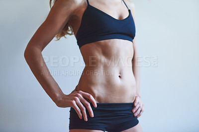 Buy stock photo Cropped shot of an unrecognizable young female athlete standing with her hands on her hips